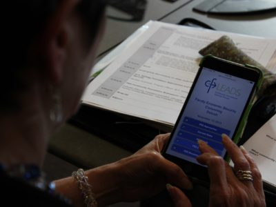 Closeup of phone with Family Economic Security event app
